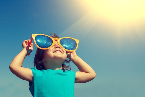 543562666 Happy little girl with big sunglasses looking at the sun.jpg